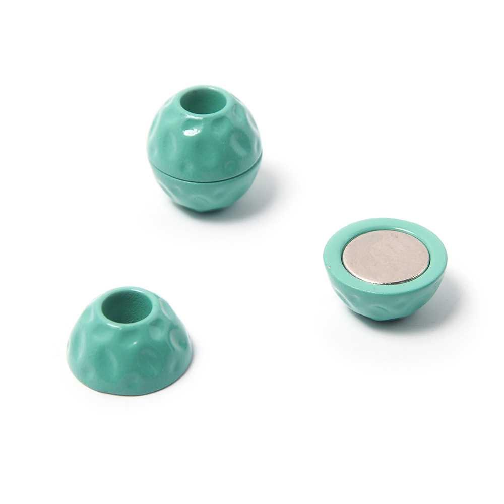 Cierre de imán pintado en color aguamarina, bola golpeada, con hueco redondo de 5 mm de diámetro.