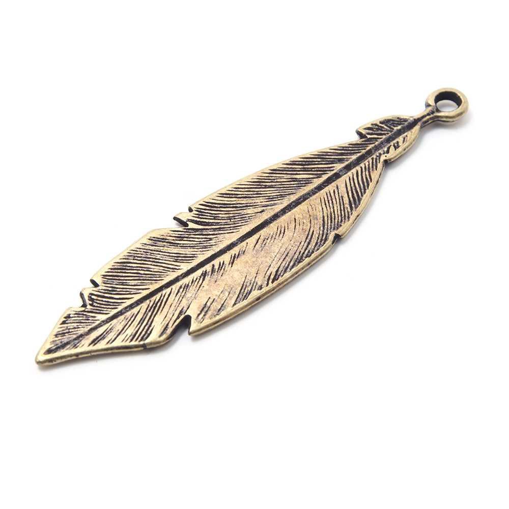 Pieza pluma grande con anilla de 2mm. de diámetro interior. Bañada en oro envejecido.