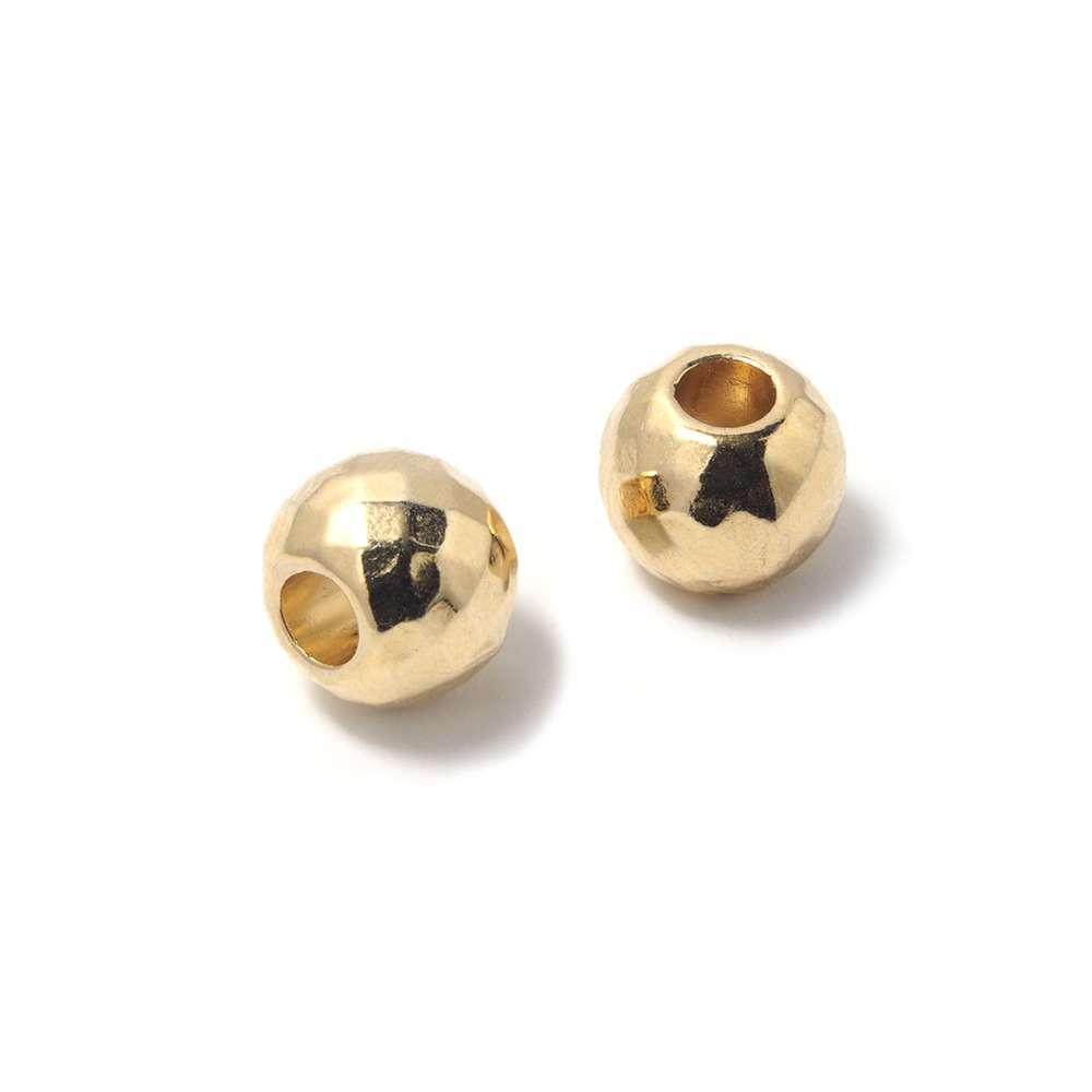 Bola mediana facetada, de 8mm de diámetro exterior, con un agujero pasante de 3mm. Bañada en oro de 24 quilates.