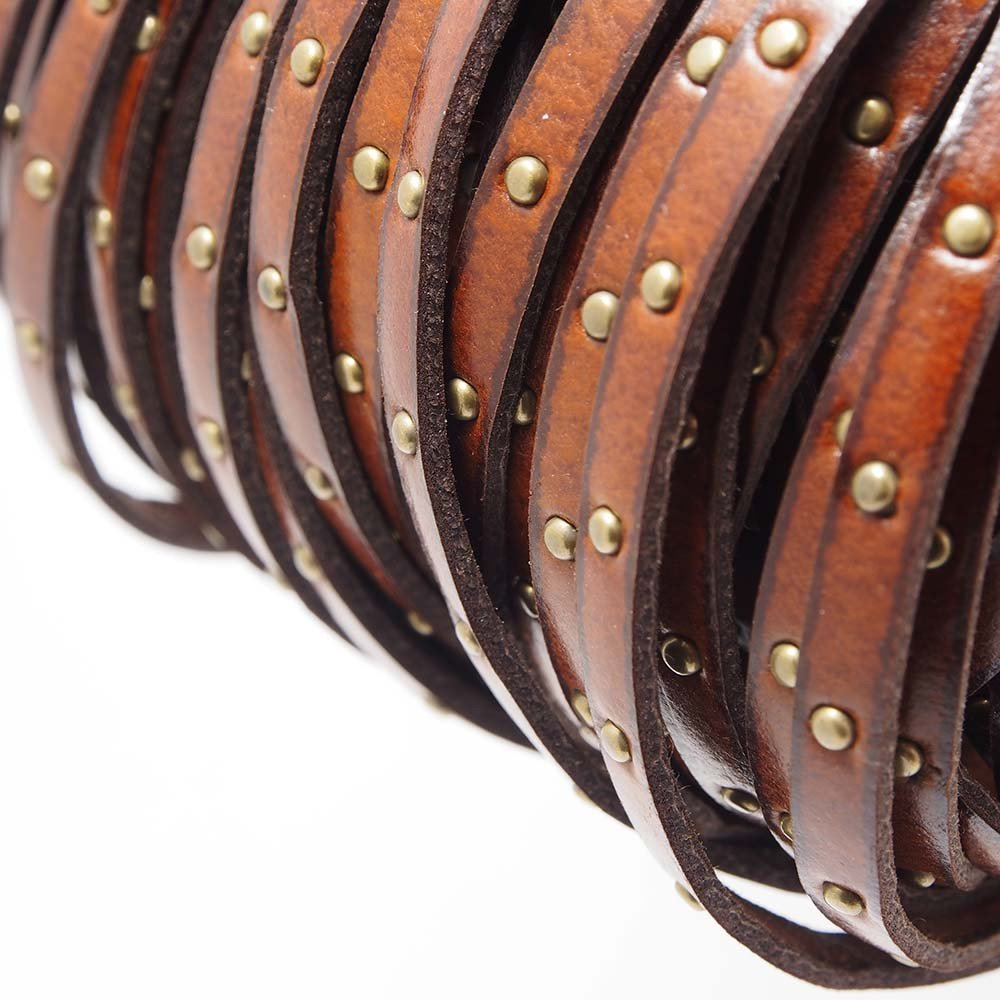 Cuero plano de 5mm de ancho por 2mm de grosor. Color marrón con tachuelas bañadas en oro envejecido.